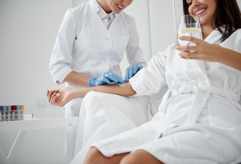 Cropped portrait of charming woman in white bathrobe sitting in armchair and receiving IV infusion. She is holding glass of lemon beverage and smiling