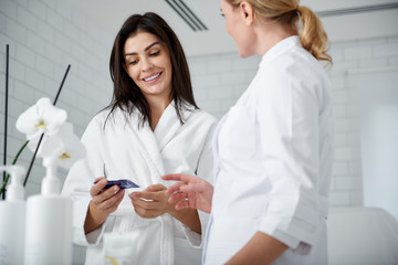 Waist up portrait of smiling woman in soft bathrobe holding sample of face cream and listening cosmetologist