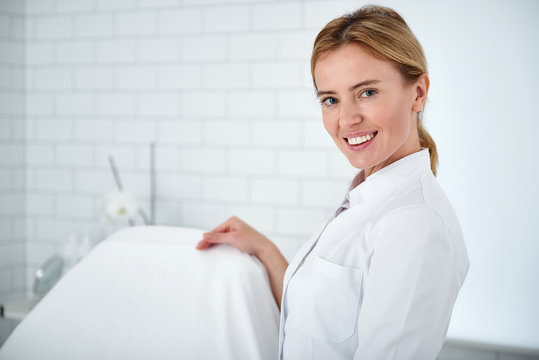 Portrait of charming beautician in white lab coat looking at camera and smiling while standing near daybed. Copy space on left side