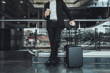 Low angle of a businessman drinking coffee while standing with his luggage at the airport