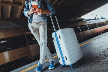 Low angle of a young man standing with his suitcase on the platform of the railway station