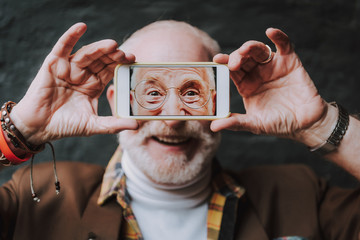 Advanced old age concept. Positive mood and inspiration with new technology. Close up portrait of happy pensioner with joyful smile while making selfie