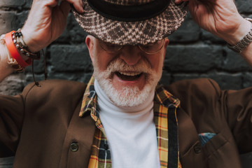Close up portrait of happy pensioner smiling and taking off his hat near black brick wall