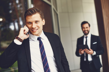 Attractive young man in elegant dark suit talking on the phone while his colleague standing not far from him