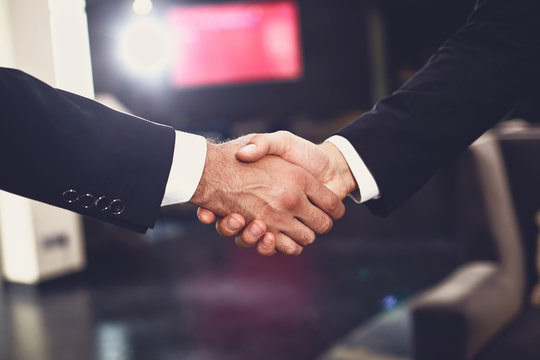 Close up of two elegant men shaking hands while meeting each other