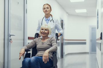 Smiling aged woman is sitting on wheelchair. Female physician is assisting her by pushing along hospital corridor. Copy space in right side