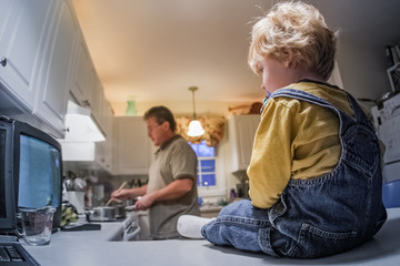 Toddler boy sitting on kitchen counter watching tv while father prepares dinner Wall mural