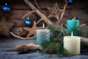 Beach scene of Christmas candles and seaside decor with ornaments on a wooden background