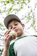 Pic of young boy holding a baseball getting read to pitch