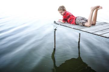 Boy laying on a dock by a lake