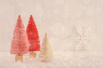 Image of miniature Christmas trees on a vintage textured wooden background