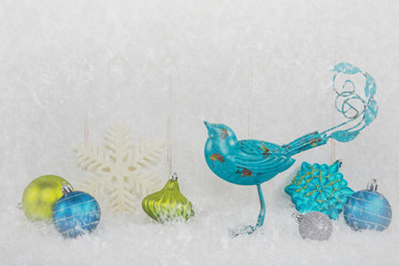 Christmas ornaments and blue bird on a snowy background