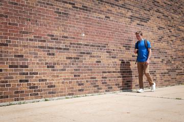 Student walking by a brick school wall