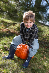 Smiling young boy with a pumpkin in autumn