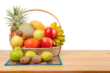 Composition with assorted fruits in wicker basket on wooden table, balanced diet, copy space