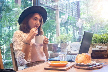 Asian women holding coffee cup looking laptop in cafe