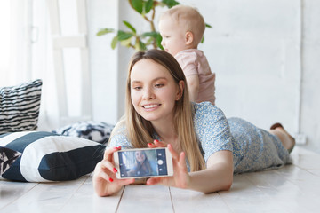 Beautiful pretty mother and her little fun smiling son playing indoor and making selfie on smartphone. Cute mom and child play at cozy home in white daylight interior. Happy family make self-portrait