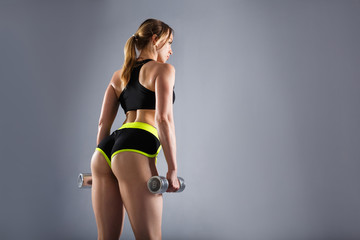 Buttocks of a beautiful young unidentified sports woman with dumbbells in her arms in a sport suit....