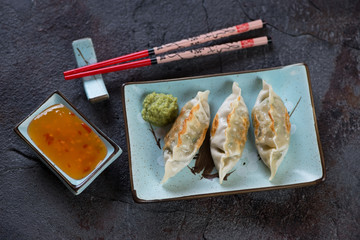 Turquoise tableware with pan fried korean dumplings, high angle view over cracked weathered asphalt background