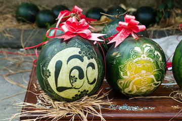 Watermelons with festive engraving on Eve of Vietnamese New Year. The inscription is translated – Clarify. Hue, Vietnam.