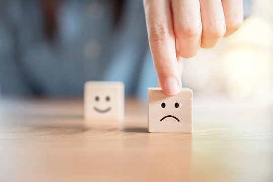 Close up customer hand choose sad face and blurred smiley face icon on wood cube, Service rating, satisfaction concept.