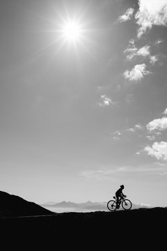 silhouette of cyclist with mountains in background