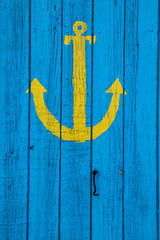 Yellow anchor  painted onto a blue wooden wall.