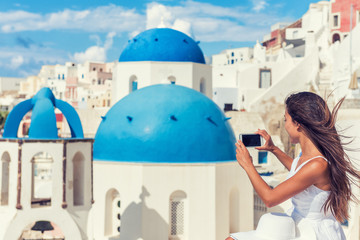 Fototapete - Travel tourist taking phone picture of Santorini Blue dome church, touristic attraction in Europe, European vacation banner. Woman taking smartphone photo of famous destination.