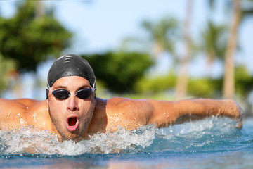 Swim training man swimmer butterfly stroke at outdoor swimming pool.. Competitive male sport athlete swimmer wearing swimming goggles and cap. Fitness sport lifestyle.