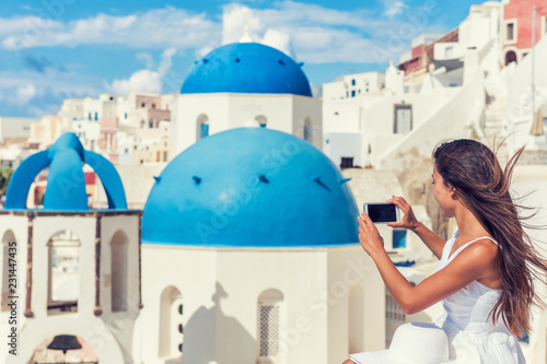 Wall mural Travel tourist taking phone picture of Santorini Blue dome church, touristic attraction in Europe, European vacation banner. Woman taking smartphone photo of famous destination.