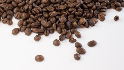 Brown, roasted coffee beans are shown up close and loosely spread out on a plain, white surface.
