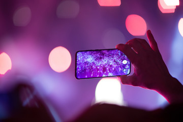 Crowd watching fireworks show and one hand recording video by new smart phone. Colorful blurry background. 29th October 2018 Izmir Turkey