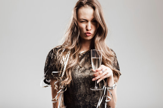 Beautiful girl dressed in stylish elegant black dress holds glass of champagne grimacing on a white background