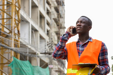 Thoughtful young black African man construction worker talking o