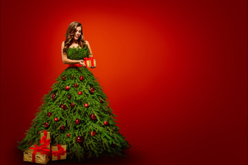 Fashion Woman in Christmas Tree Dress, Model hold Xmas Present Gifts over New Year Red Background