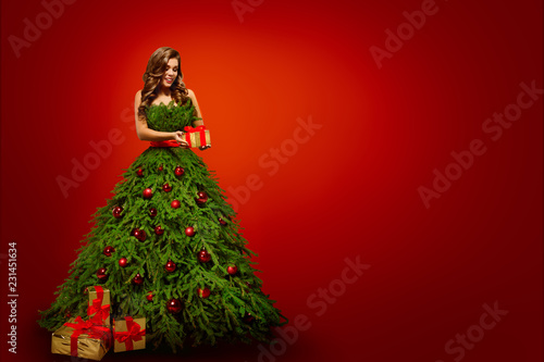 fashion woman in christmas tree dress model hold xmas present gifts over new year red