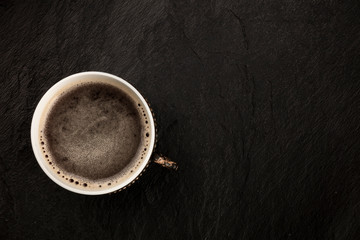 A photo of black coffee in a vintage cup, shot from above on a black slate background with copy space