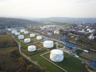 Huge tanks with fuel and flammable substances on the territory of the refinery. View from the drone at a height of bird flight. The production of gasoline removed from aircraft. Oil refining industry.