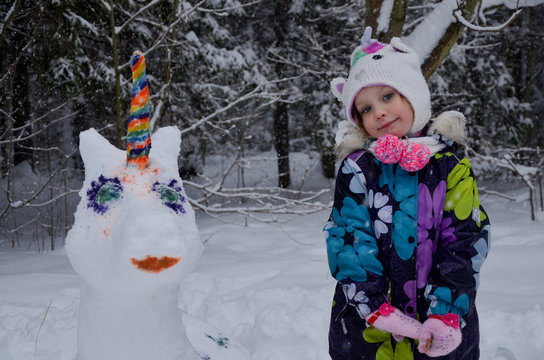 girl with painted snow unicorn in winter