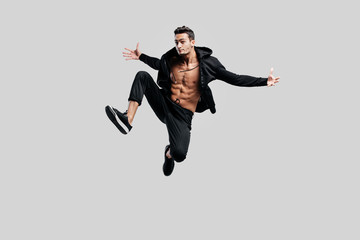 Handsome dancer of street dancing dressed in black pants and a sweatshirt on a naked torso jumps and spreads his arms to the sides