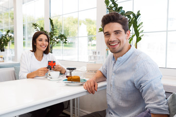 Loving couple sitting in cafe eat desserts and drinking tea.