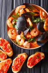Delicious tomato soup bouillabaisse with shrimps, fish fillets and mussels closeup in a bowl. Vertical top view