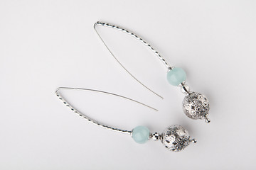 silver earrings blue agate stone white background
