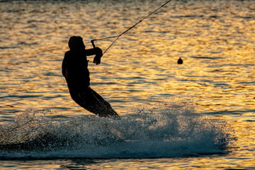 Silhouette of a wakeboarder at sunset.