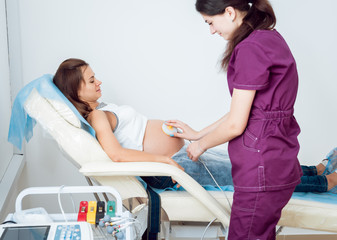 Pregnant woman with electrocardiograph check up for her baby. Fetal heart monitoring