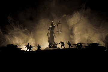 War - no justice concept. Military silhouettes fighting scene and The Statue of Justice on a dark toned foggy background.