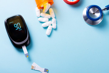 White pills in orange bottle with blood glucose meter on blue background with copy space