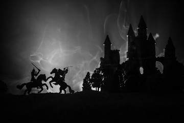 Silhouettes of figures as separate objects, fight between warriors on dark toned foggy background with old gothic castle