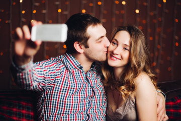 Happy and positive couple making self portrait in decorated for Christmas studio. Handsome husband embracing and kissing attractive wife, taking photo at smartphone.