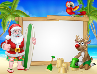 Santa Claus Christmas cartoon character in shorts and flip flops holding his surfboard on a tropical beach with his reindeer making sandcastles sign background.